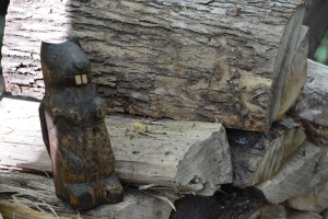 wooden beaver carving on woodpile